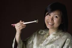 A woman in a kimono eating sushi Stock Photos