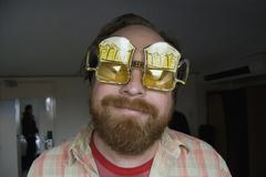 A young man wearing sunglasses made to look like two mugs of beer Stock Photos