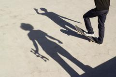 Shadows on two skateboarders on concrete - stock photo