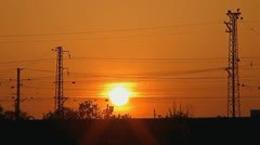 005 sunset of a sun above the line of electricity transmissions 1 min Stock Footage