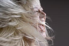 Stock Photo of A woman tossing her hair with her mouth open