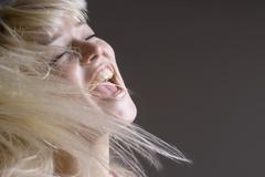 A woman tossing her hair with her mouth open Stock Photos
