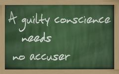 """Stock Photo of """" a guilty conscience needs no accuser """" written on a blackboard"""