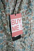 'Buy Me!' price tag hanging from a lady's blouse Stock Photos