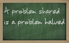 """ a problem shared is a problem halved "" written on a blackboard Stock Photos"