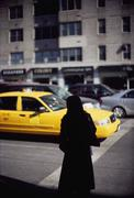 A silhouetted person standing on a city street as a yellow taxi drives by Stock Photos