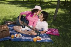 A young couple having a picnic together and playing a guitar Stock Photos