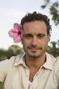 Portait of a man wearing a tropical flower Stock Photos