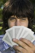 Stock Photo of A man looking from behind a hand of cards