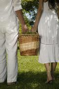 A young couple holding a basket together Stock Photos