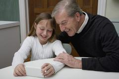 A granddaughter using a electronic device while her grandfather watch - stock photo