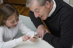 A granddaughter using a electronic device while her grandfather watch Stock Photos