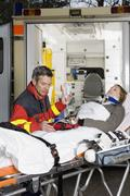 A paramedic assisting a woman in front of an ambulance - stock photo
