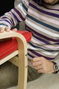 A man using a Allen wrench to tightening a screw on a chair Stock Photos