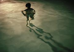 A young woman standing in a swimming pool at night, silhouette Stock Photos