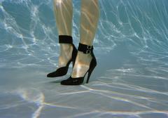A woman's legs wearing high heels underwater Stock Photos