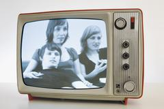 A televison with a black and white image of three young people Stock Photos