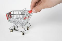 A miniature empty shopping cart being pushed by human fingers Stock Photos