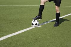 A young man on a soccer field with his foot on a soccer ball, low section Stock Photos