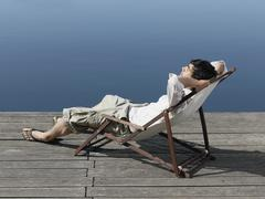 A young man sitting in a deck chair on a jetty - stock photo