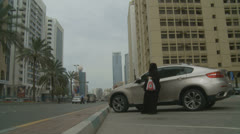 Lady wearing Burqa gets into car, Abu Dhabi Stock Footage