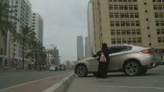 Lady wearing Burqa gets into car, Abu Dhabi Stock Footage
