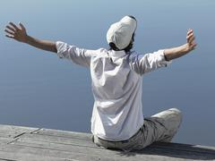 A young man sitting on a jetty with his arms stretched out Stock Photos
