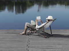 A young man sitting in a deck chair on a jetty reading a book - stock photo