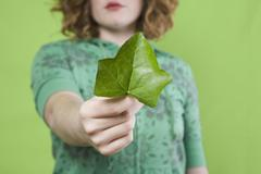 A young woman presenting an ivy leaf Stock Photos