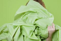 A young woman holding a large green paper in front of her Stock Photos