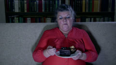 Fat senior woman watching tv show and eating cake - stock footage