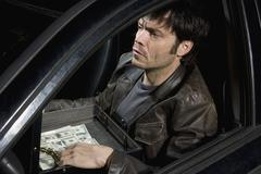 A man sitting in a car with an open briefcase full of money Stock Photos