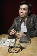 A man sitting at a table with stacks of money, a mobile phone and a hard drive - stock photo