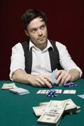 A man looking suspiciously at a high stakes poker game Stock Photos
