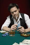 Stock Photo of A man at a high stakes poker game looking at his hand of cards