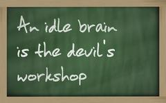 """ an idle brain is the devil's workshop "" written on a blackboard Stock Photos"