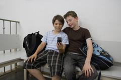 Two pre-adolescent boys sitting on a bench looking at a mobile phone - stock photo