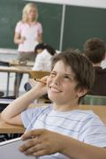 A pre-adolescent boy sitting in the back of a classroom, looking up in - stock photo