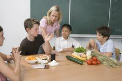 A teacher and four students learning about nutrition Stock Photos