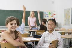 Two pre-adolescent girls sitting in the back of a classroom, looking at camera Stock Photos