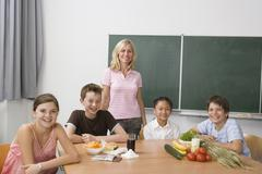A teacher and four students learning about nutrition - stock photo