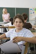 A pre-adolescent boy sitting in the back of a classroom, looking at camera Stock Photos