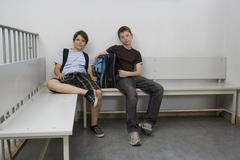 Two pre-adolescent boys sitting on a bench - stock photo