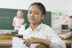 A pre-adolescent girl sitting in the back of a classroom, looking at camera - stock photo