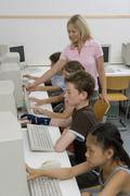 A teacher and four pre-adolescent children in a computer lab - stock photo