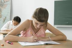 A pre-adolescent girl studying in a classroom - stock photo