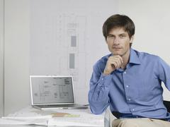 An architect sitting at his desk with a laptop and architectural drawings Stock Photos