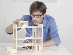 An architect examining an architectural model - stock photo