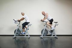 A senior woman and a mature man riding stationary bikes Stock Photos
