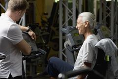 A senior woman on a stationary bike learning from an instructor Stock Photos